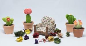 Juguete del sofá en el jardín con cualquier flores y pequeño árbol en blanco imágenes de archivo libres de regalías