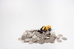 juguete del tractor que rastrilla encima de monedas Fotos de archivo