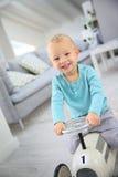 Juguete feliz del coche del montar a caballo del niño pequeño en casa Imagen de archivo