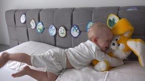 Juguete feliz del conejo del abrazo del muchacho en cama El muchacho activo se divierte con el conejito grande de la felpa en cam almacen de video