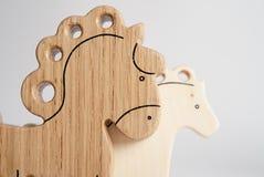 Juguete hecho a mano de madera del caballo para los niños en el fondo blanco con la reflexión de la sombra Bellota de madera para Fotografía de archivo