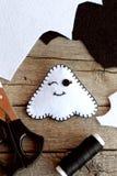 Juguete lindo del fantasma de Halloween del fieltro, tijeras, hilo negro, pedazos del fieltro en viejo fondo de madera Fuentes pa Fotos de archivo