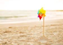 Juguete olorful del molino de viento del  de Ñ que se coloca en la playa Fotografía de archivo