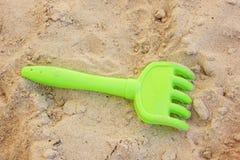 Juguete plástico de la bifurcación de la playa en arena foto de archivo