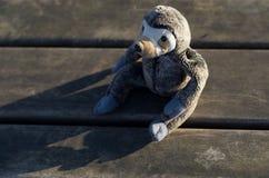 Juguete relleno del mono en banco fotografía de archivo