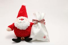 Juguete relleno lindo Santa Claus y presente en el fondo blanco Fotografía de archivo