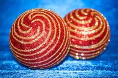 Juguete rojo de la Navidad con las rayas del oro en un primer azul del fondo Año Nuevo, fondo de la Navidad Fotografía de archivo