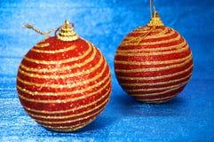 Juguete rojo de la Navidad con las rayas del oro en un primer azul del fondo Año Nuevo, fondo de la Navidad Foto de archivo libre de regalías