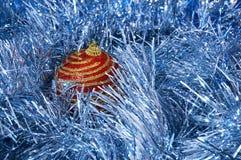 Juguete rojo de la Navidad con las rayas del oro en un primer azul del fondo Año Nuevo, fondo de la Navidad Imagen de archivo libre de regalías