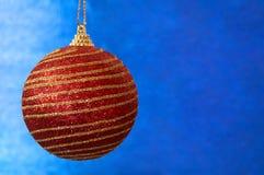 Juguete rojo de la Navidad con las rayas del oro en un primer azul del fondo Año Nuevo, fondo de la Navidad Imagen de archivo