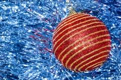 Juguete rojo de la Navidad con las rayas del oro en un primer azul del fondo Año Nuevo, fondo de la Navidad Fotos de archivo
