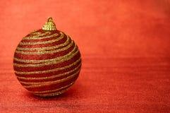 Juguete rojo de la Navidad con las rayas del oro en un primer rojo del fondo Año Nuevo, fondo de la Navidad Imagen de archivo