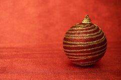 Juguete rojo de la Navidad con las rayas del oro en un primer rojo del fondo Año Nuevo, fondo de la Navidad Imagenes de archivo