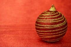 Juguete rojo de la Navidad con las rayas del oro en un primer rojo del fondo Año Nuevo, fondo de la Navidad Imágenes de archivo libres de regalías