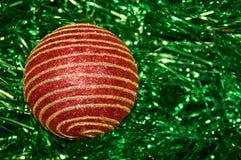 Juguete rojo de la Navidad con las rayas del oro en un primer verde del fondo Año Nuevo, fondo de la Navidad Foto de archivo