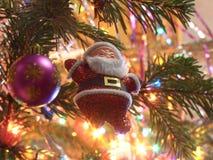 Juguete Santa en el árbol de navidad Fotos de archivo libres de regalías