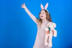 Juguete sonriente del conejito del juego del niño Niñez feliz Consiga en el alcohol de pascua Accesorio de los oídos del conejito imágenes de archivo libres de regalías