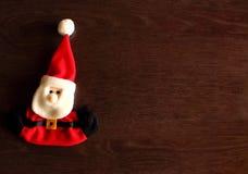 Juguete suave Santa Claus para el árbol del Año Nuevo en fondo de madera con el espacio de la copia como las vacaciones de invier Foto de archivo