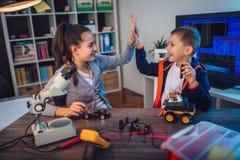 Juguete técnico sonriente feliz de las construcciones del muchacho y de la muchacha y hacer el robot foto de archivo