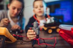 Juguete técnico sonriente feliz de las construcciones del muchacho y de la muchacha y hacer el robot fotos de archivo