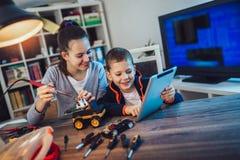 Juguete t?cnico sonriente de las construcciones del muchacho y de la muchacha y hacer el robot Juguete t?cnico en la tabla por co fotografía de archivo libre de regalías
