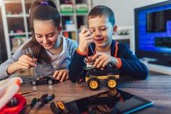 Juguete t?cnico sonriente de las construcciones del muchacho y de la muchacha y hacer el robot Juguete t?cnico en la tabla por co imagen de archivo