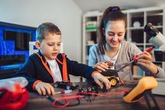 Juguete t?cnico sonriente de las construcciones del muchacho y de la muchacha y hacer el robot Juguete t?cnico en la tabla por co fotos de archivo libres de regalías
