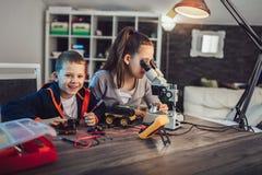 Juguete t?cnico sonriente de las construcciones del muchacho y de la muchacha y hacer el robot Juguete t?cnico en la tabla por co imágenes de archivo libres de regalías