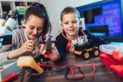 Juguete t?cnico sonriente de las construcciones del muchacho y de la muchacha y hacer el robot Juguete t?cnico en la tabla por co imagenes de archivo
