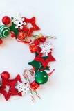 Juguetes blancos rojos del día de fiesta de la guirnalda de la Feliz Navidad Fotos de archivo