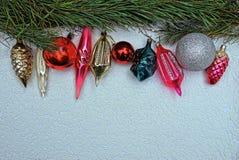 Juguetes brillantes del ` s del Año Nuevo y ramas del pino en un fondo gris Fotografía de archivo