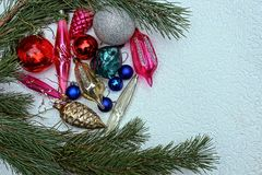 Juguetes brillantes del ` s del Año Nuevo y ramas del pino en un fondo gris Foto de archivo