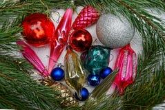 Juguetes coloreados brillantes del ` s del Año Nuevo y ramas del pino en un fondo gris Foto de archivo