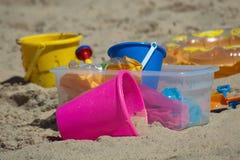 Juguetes coloridos de los niños en la playa Imágenes de archivo libres de regalías
