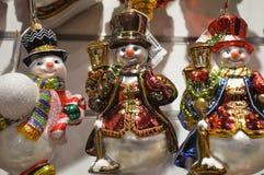 Juguetes coloridos del Año Nuevo, Niza muñecos de nieve en una ventana de la tienda Imagen de archivo libre de regalías