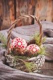 Juguetes, conos y nueces de la Navidad en la cesta cerca del suéter Foto de archivo libre de regalías