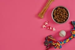 Juguetes - cuerda coloreada multi, bola, comida seca y hueso Accesorios para el juego en la opinión superior del fondo rosado Foto de archivo libre de regalías