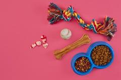 Juguetes - cuerda coloreada multi, bola, comida seca y hueso Accesorios para el juego en la opinión superior del fondo rosado Fotografía de archivo libre de regalías
