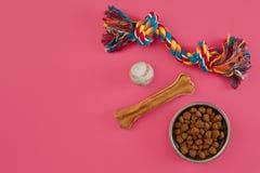 Juguetes - cuerda coloreada multi, bola, comida seca y hueso Accesorios para el juego en la opinión superior del fondo rosado Fotografía de archivo