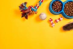Juguetes - cuerda coloreada multi, bola y comida seca Accesorios para el juego en la opinión superior del fondo amarillo Foto de archivo libre de regalías