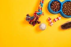 Juguetes - cuerda coloreada multi, bola y comida seca Accesorios para el juego en la opinión superior del fondo amarillo Foto de archivo