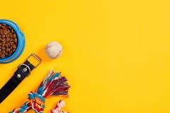 Juguetes - cuerda coloreada multi, bola y comida seca Accesorios para el juego en la opinión superior del fondo amarillo Imágenes de archivo libres de regalías