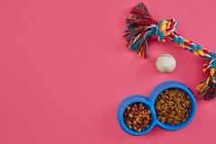 Juguetes - cuerda coloreada multi, bola y comida seca Accesorios para el juego en la opinión superior del fondo rosado Imagen de archivo