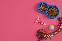 Juguetes - cuerda coloreada multi, bola y comida seca Accesorios para el juego en la opinión superior del fondo rosado Foto de archivo