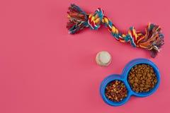 Juguetes - cuerda coloreada multi, bola y comida seca Accesorios para el juego en la opinión superior del fondo rosado Fotos de archivo libres de regalías