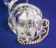 Juguetes de cristal blancos de un carámbano, cinta a del ` s del Año Nuevo del regalo en un fondo azul Fotografía de archivo