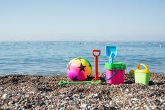 Juguetes de la bola, de los cubos, del rastrillo y de la pala en una playa cerca del s Imágenes de archivo libres de regalías