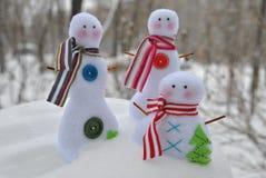 Juguetes de la familia de los muñecos de nieve en la nieve Foto de archivo libre de regalías