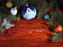 Juguetes de la Navidad y ramas del abeto en la tabla de madera Imágenes de archivo libres de regalías