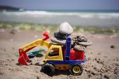 Juguetes de la playa con las piedras en arena Imagenes de archivo